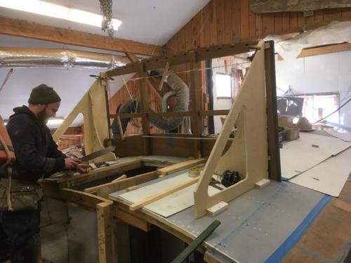 Setting the windshield frame into place around the companionway